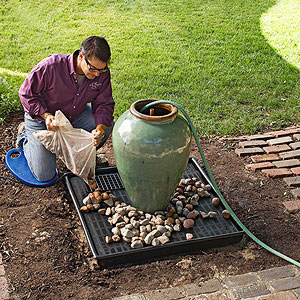 Fill the urn with water, cover the grate with rocks, and plug in the pump.