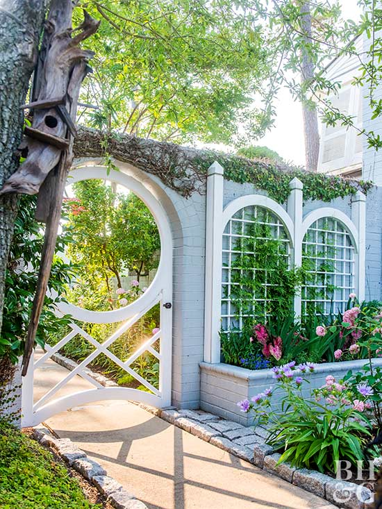 Gloriously Gothic In Style, A Pair Of Arched Garden Trellises Echo The  Shape And Details Of A Doorlike Gate. Showcased Against Blue Painted Brick  Walls, ...
