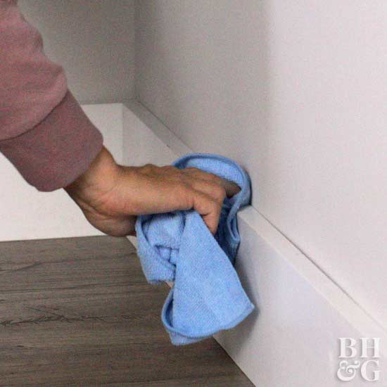 wiping off baseboard with cloth