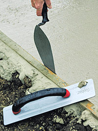 Slip trowel between form and concrete