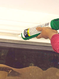 Apply caulk along sill flange