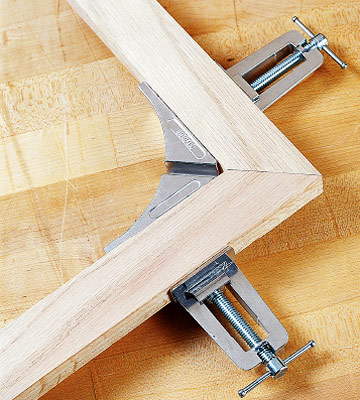Ninety degree corner clamps holding two pieces of wood for a frame