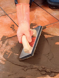 Pack grout into joints