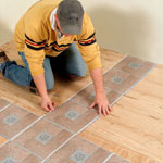 Man Installing Decorative Tile on Wood Floor