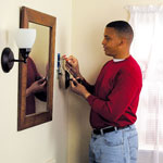 Man Installing Bathroom Light Fixture