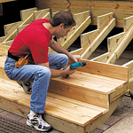 man attaching deck steps with screwdriver