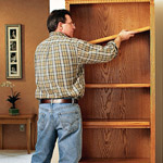 man adjusting shelves