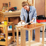 woman staining end table