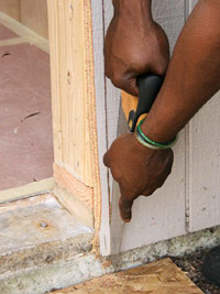 Finish cutting siding with handsaw