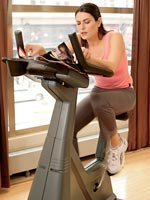 woman hunched over on exercise bike