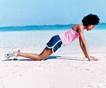 woman doing push up on beach