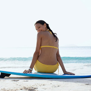Woman sitting on surf board