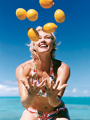 woman in bikini juggling lemons