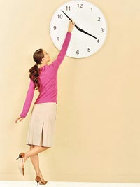 Woman adjusting wall clock