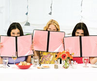 3 women holding menus in front of their faces