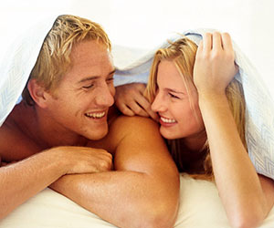 man and woman smiling at each other in bed