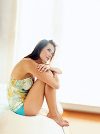 seated woman in pajamas holding knees to chest