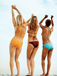 three women in bikinis dancing on beach
