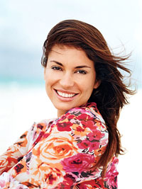 brunette woman smiling in floral shirt