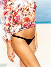 torso and legs of woman in floral shirt and black bikini bottoms