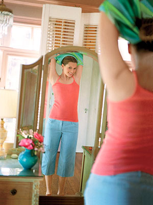 woman taking off shirt in front of bedroom mirror