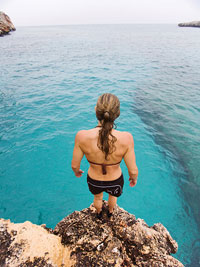 woman standing on cliff looking down at ocean