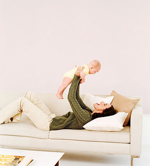 woman lying on couch holding infant