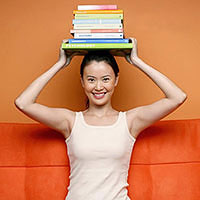 Woman holds books over her head
