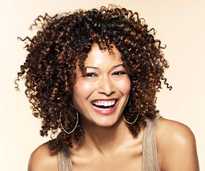 woman smiling, brown curly hair, medium length haircuts, hairstyles for medium hair, medium layered haircuts, medium hairstyles with bangs, medium haircuts for women