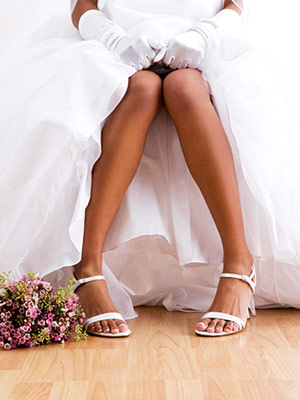 bride sitting on bed, holding up dress