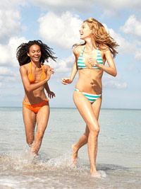 two women in bikinis running on the beach