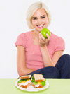 woman eating apple with sandwich for lunch