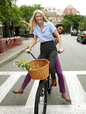 two women on a bike, wearing skinny jeans