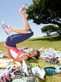 woman rolling on glass surrounded by running shoes