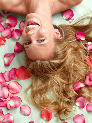 model lying on bed with rose petals