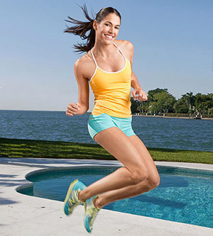 woman jumping up by the pool