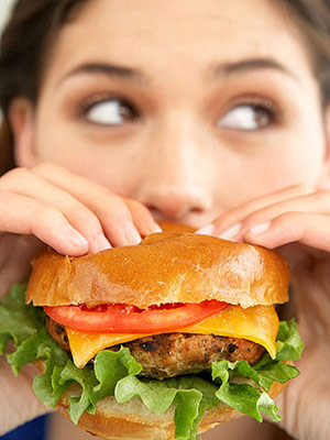 Woman eating cheeseburger