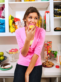 woman eating cupcake in the kitchen