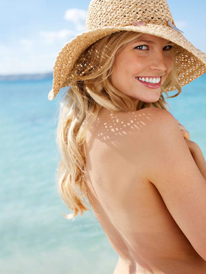 back of woman wearing a hat on the beach