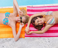 women lying on beach towels