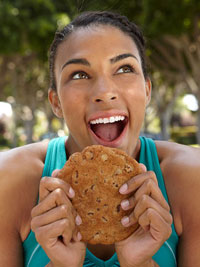 woman in workout clothes eating cookie