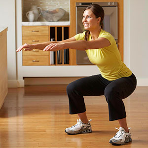 woman doing squat in kitchen