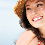 woman wearing a sun hat, smiling