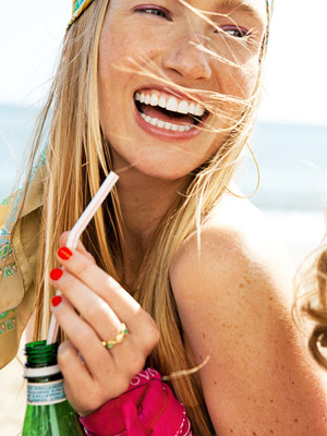 model laughing and drinking out of a straw