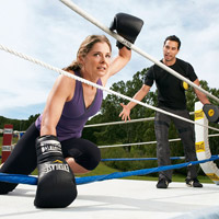 woman and trainer in boxing ring