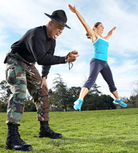 woman with trainer doing jumping jacks