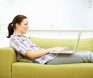 Woman laying on couch with laptop on lap