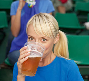 Woman drinking beer in a baseball stadium