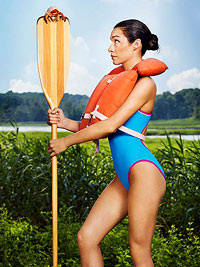 Girl in life jacket holding paddle with crab on top.