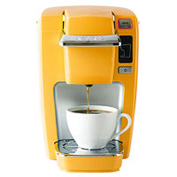 Yellow Keurig pouring coffee into cup